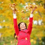 Happy fall woman throwing leaves